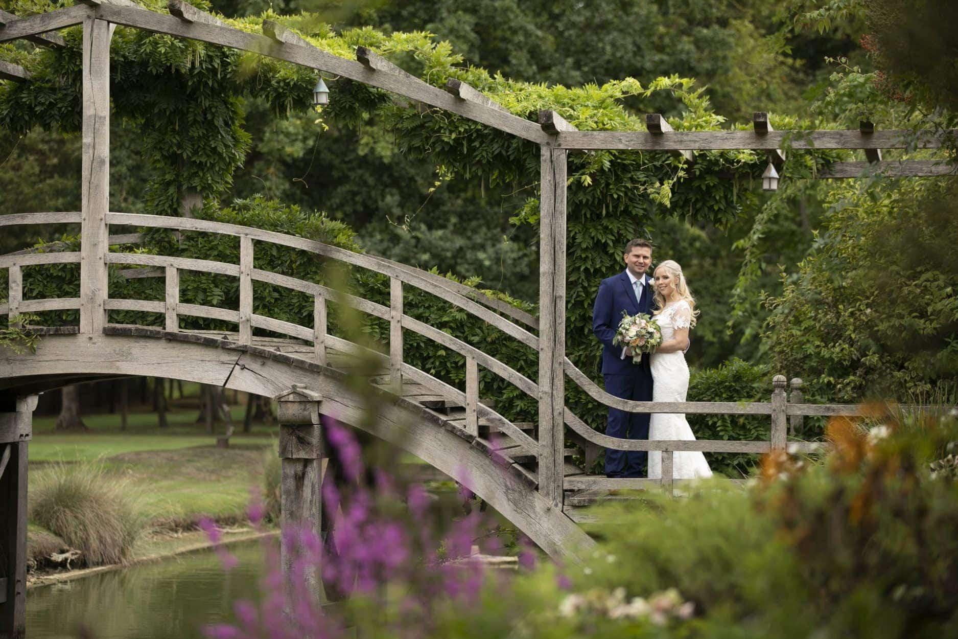Ruth in Amanda Wyatt Honesty Wedding Dress on a bridge with her husband