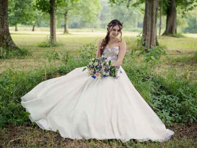 Blossom by Lyn Ashworth is a ball gown wedding dress with silver lilac and green florals, fitted & boned bodice, flowing skirt and ice blue silk sash