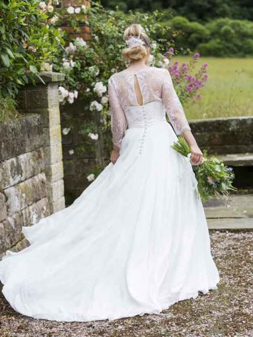 Farewell to Spring by Lyn Ashworth is a ball gown wedding dress with a billowing skirt, boned bodice and a delicately soft ivory pink lace jacket
