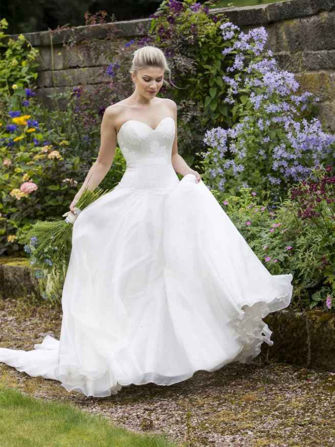 Porcelain Rose by Lyn Ashworth is a ball gown wedding dress, dropped waist boned bodice, overlaid with rose lace and a full, swishy skirt.